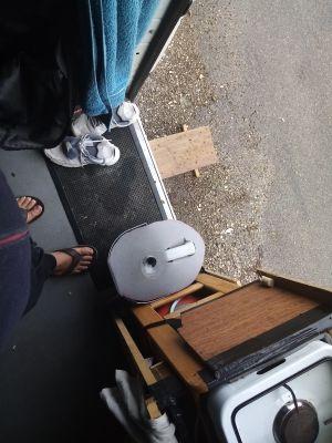 Ce truc gris c'est le collecteur de mes eaux de vaisselle et salle de bains. C'est un bidon de 5 litres posé dans un seau et recouvert d'un bout de lino, avec un entonnoir hacké.